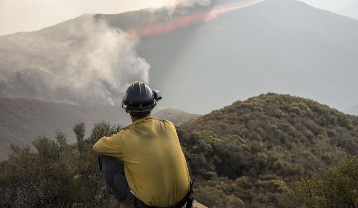 A firefighter watches a 2017 blaze in California. (California National Guard/Flickr)